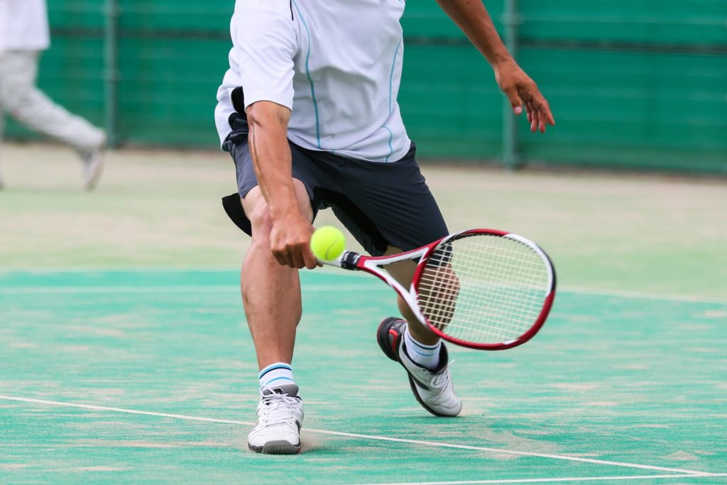 スポーツのテニスで膝を曲げて打つ動き